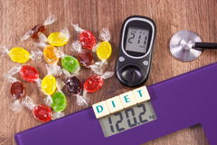 Electronic bathroom scale and glucometer with result of measurement and colorful candies, diabetes, slimming and reduction eating Stock Photo