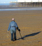 Electronic beach combing. Woman beach combing with a metal detector on a winters day royalty free stock photography