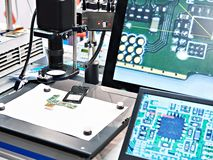 Electronic boards and chips, industrial microscope. And monitors royalty free stock photo
