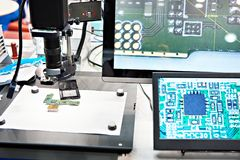 Electronic boards, microscope and monitors. Electronic boards and chips, industrial microscope and monitors stock images