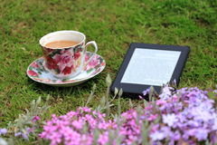 An electronic book reader and a cup of coffee on the grass. Books, technology and nature. Electronic book reader Stock Images
