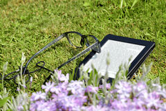 An electronic book reader and glasses on the grass. Books, technology and nature. Electronic book reader Royalty Free Stock Photos