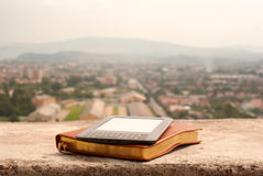 Electronic book reader laying on the book Royalty Free Stock Image