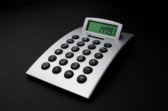 Electronic calculator. An electronic calculator on a black stock images