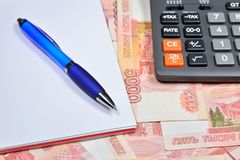 Electronic calculator and blue pen with notebook lying on the ba. Nknotes of five thousand rubles. Business still life Royalty Free Stock Photography