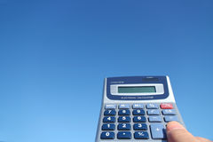 Electronic calculator and the hand in the blue sky Stock Photography