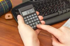 Electronic calculator in the hand of schoolboy over the desktop. Modern electronic pocket calculator with a liquid-crystal display in the hand of schoolboy on a Stock Images