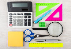 Electronic calculator, magnifying glass and miscellaneous statio Stock Photos