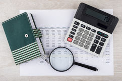 Electronic calculator, magnifying glass and notepad with pen on Royalty Free Stock Photos