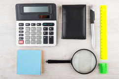 Electronic calculator and miscellaneous stationery tools on wood Royalty Free Stock Photos