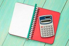 Electronic calculator and notebook. Royalty Free Stock Photo