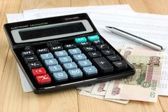Electronic calculator, pen and Russian money on sheets of paper Royalty Free Stock Photo