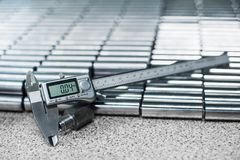 Electronic caliper in front of bearing rollers. Close up, depth of field, selective focus. Electronic caliper. Close up, depth of field, selective focus stock photo