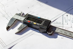 Electronic caliper lies on a engineering drawings royalty free stock images