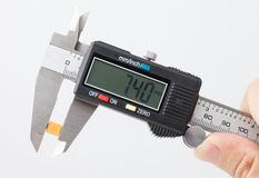 Electronic caliper measure yellow capacitor Royalty Free Stock Images