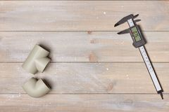 Electronic calipers with plastic pipes on wooden table stock photography