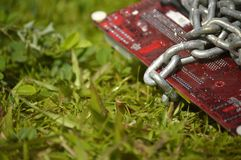 Electronic card chained on grass. Royalty Free Stock Images