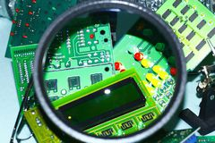 Electronic circuit boards on a blue background plus a magnifying glass. Electronic cards on a blue background shot through a round magnifying glass, well drawn stock photos