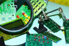 Electronic circuit boards on a blue background plus a magnifying glass. Electronic cards on a blue background shot through a round magnifying glass, well drawn stock image