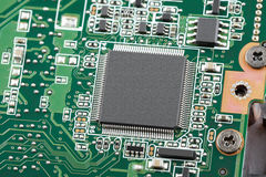 Electronic chip on a green circuit board. Close-up top view Stock Image