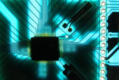 Electronic chip and cicuit board. An electronic chip mounted on a circuit board with copper tracks and the photo has been lit from the background in greenish stock photos