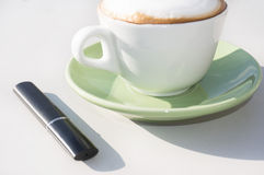 Electronic cigar and cup of cappuccino Stock Image