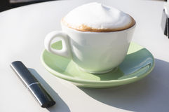 Electronic cigar and cup of cappuccino Royalty Free Stock Photos
