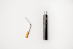 Electronic cigarette against analog cigarettes is much better gloss chrome metal. Near the broken conventional cigarettes from which the tobacco poured Stock Image