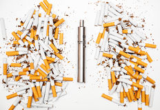 Electronic cigarette against analog cigarettes is much better gloss chrome metal. Near the broken conventional cigarettes from which the tobacco poured Royalty Free Stock Photography