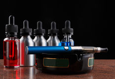 Electronic cigarette on the ashtray and bottles with vape liquid on black background Stock Image