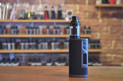 Electronic cigarette on a background of vape shop. E-cigarette for vaping stock photos