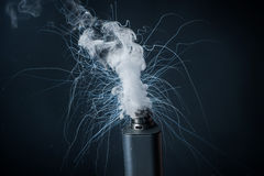 Electronic Cigarette on a black background and smoke from it Stock Photos