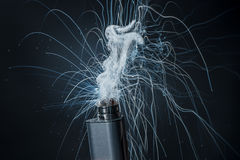 Electronic Cigarette on a black background and smoke from it Stock Photography