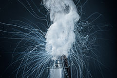 Electronic Cigarette on a black background and smoke from it Stock Images