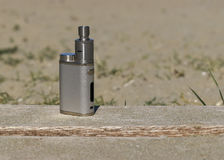 Electronic cigarette on the boards. On the background of sand Stock Photography