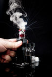 Electronic cigarette with 2 bottles and cloud of smoke. RDA Mage coilart tank with 2 liquid bottles,cotton stripe, coil and a small screwdriver on black studio Stock Image