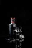 Electronic cigarette with 2 bottles. RDA Mage coilart tank with 2 liquid bottles,cotton stripe, coil and a small screwdriver on black studio background Royalty Free Stock Photography