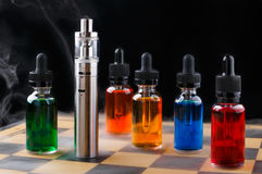 Electronic cigarette and bottles with vape liquid within vapor on chessboard and black background. Electronic cigarette and bottles with assorted vape liquid stock photo
