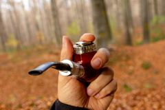E-pipe with blurred background in man`s left hand in natural ambient. stock photo
