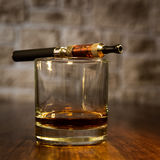 Electronic cigarette and a glass of bourbon Royalty Free Stock Image