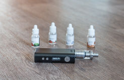 Electronic cigarette with liquids close up Stock Photos