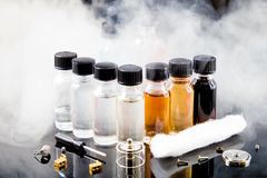 Electronic cigarette liquids with smoke on background Stock Photography