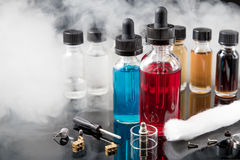 Electronic cigarette liquids with smoke on black background. Vaporizer smoke with juice bottles, screwdriver and cotton wick with tools Stock Images