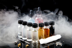 Electronic cigarette liquids with smoke on black background Royalty Free Stock Photography