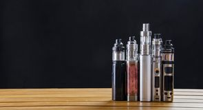 Electronic cigarette mods for ecig over a wooden background. vape devices and cigarette. Popular vaping e cig devices mod.electronic cigarette over a wood royalty free stock images
