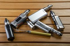 Electronic cigarette mods for ecig over a wooden background. vape devices and cigarette. Popular vaping e cig devices mod.electronic cigarette over a wood stock photos