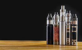 Electronic cigarette mods for ecig over a wooden background. vape devices and cigarette. Popular vaping e cig device mod.electronic cigarette over a wood royalty free stock photo