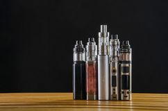Electronic cigarette mods for ecig over a wooden background. vape devices and cigarette. Popular vaping e cig device mod.electronic cigarette over a wood stock photo