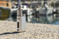Electronic cigarette on the stones. On the background of port royalty free stock image