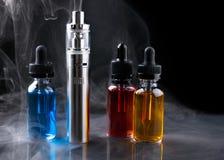 Electronic cigarette and vape liquids within vapor on black background Stock Images